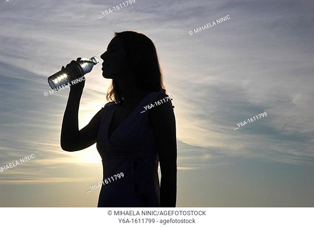 Silhouette of young woman drinking bottle of water