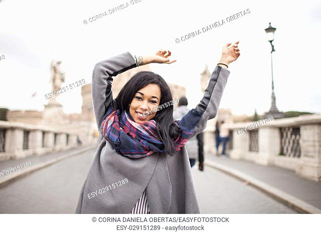 Happy cheerful young woman with arms raised, on Sant Angelo bridge in Rome Italy. Backlight shot with copy space