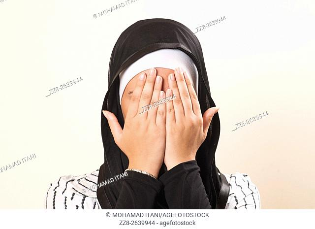 Muslim woman hiding face with hands