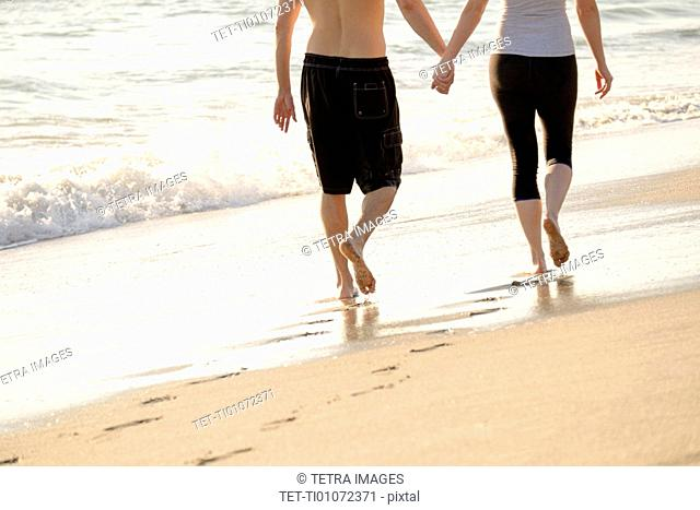 Couple walking on beach, low section