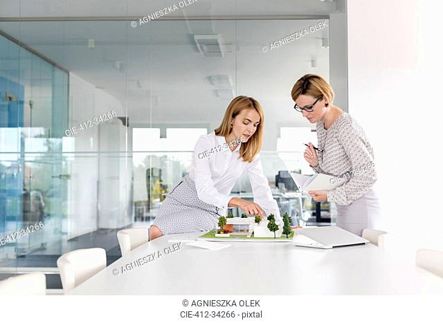 Female architects discussing model in conference room meeting