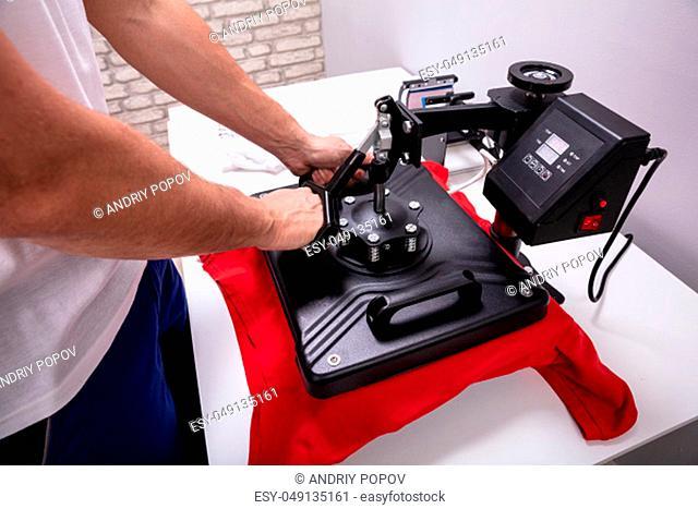 Man printing on t shirt in workshop