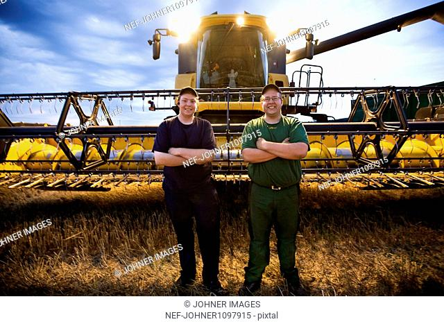 Two farmers standing in front of combine