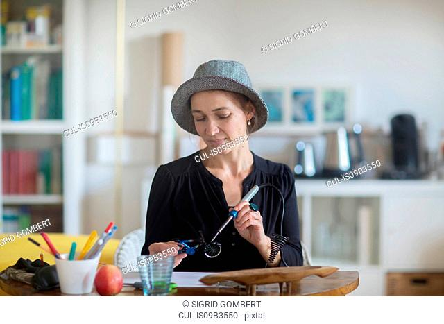 Mature woman sitting at desk, using soldering iron