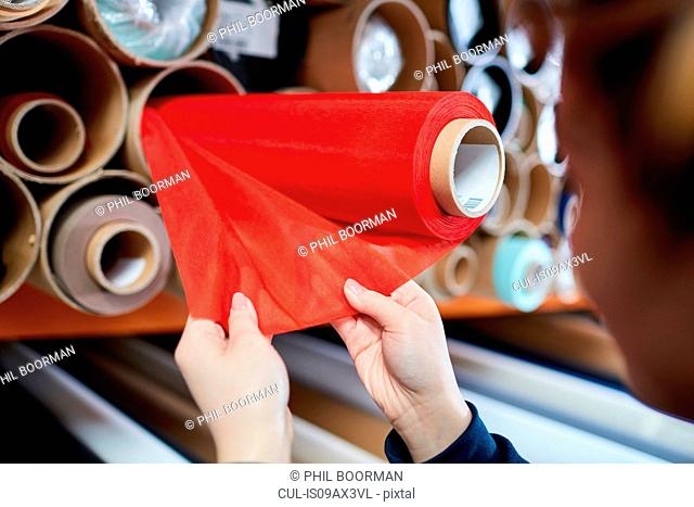Hands of female worker examining red fabric for roller blind in factory
