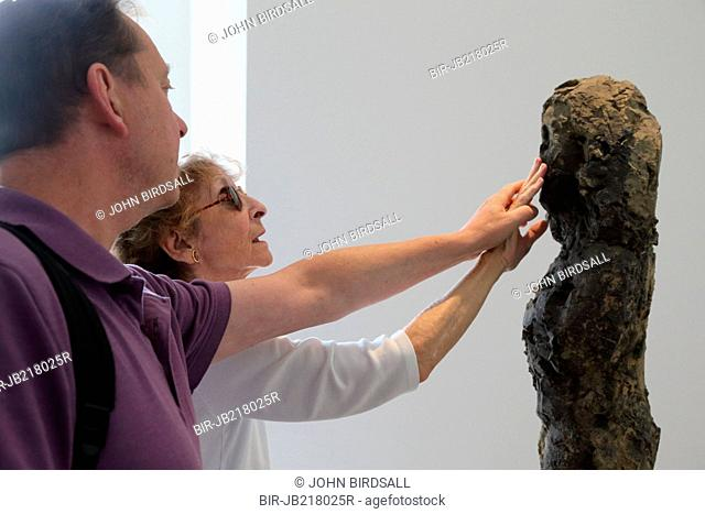 Woman with visual impairment touching a sculpture at Yorkshire Sculpture Park