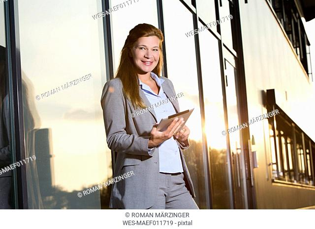 Portrait of businesswoman with digital tablet at evening twilight
