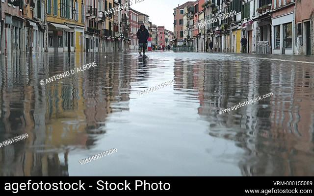 "People walking in Via Giuseppe Garibaldi, a major street in Castello Quarter, during during the so called """"acqua alta"""" high tide. Venezia. Italy"