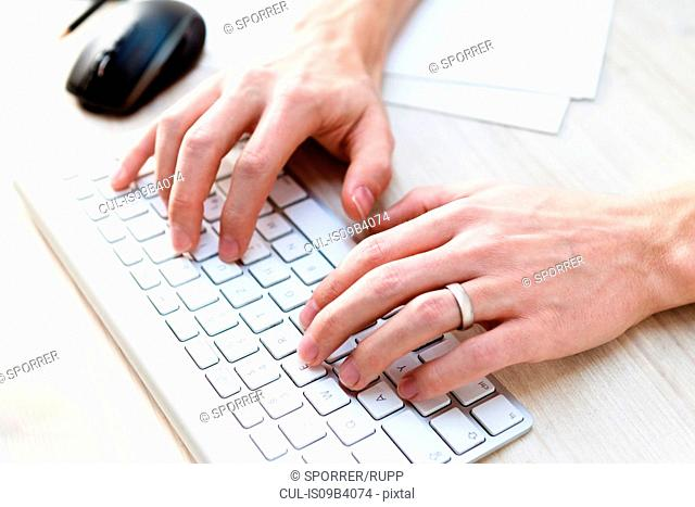 Male hands typing on computer keyboard