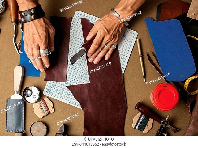 Moments of modelling design of custom made pocketbook. Workplace of Leather designer. Hands of designer craftsperson draw a pattern of wallet design on genuine...