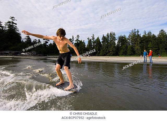 teenage boy skim boards on wet sand, MacKenzie Beach at Tofino, Vancouver Island, British Columbia, Canada