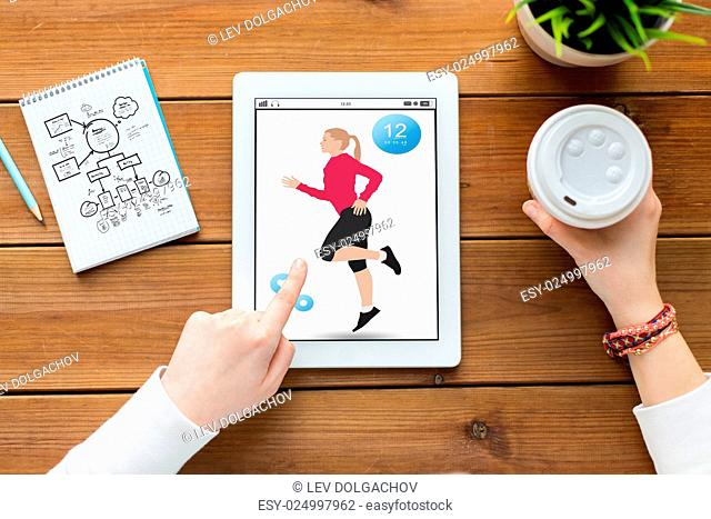 sport, technology and people concept - close up of woman with fitness application on tablet pc computer screen, notebook and coffee on wooden table