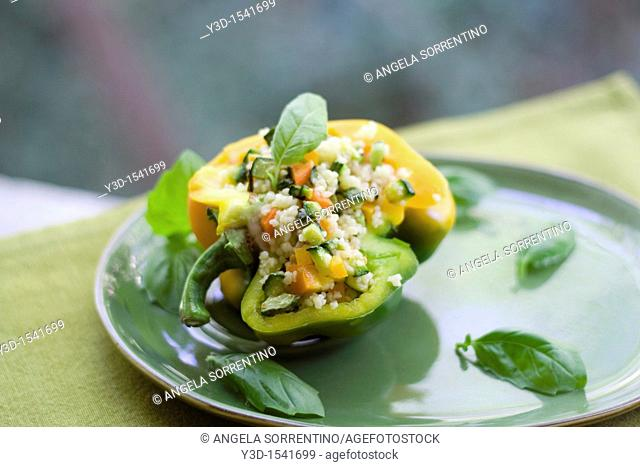 Stuffed peppers with couscous, fresh vegetables and basil