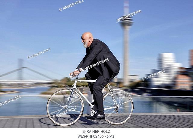 Elegant businessman riding racing bike
