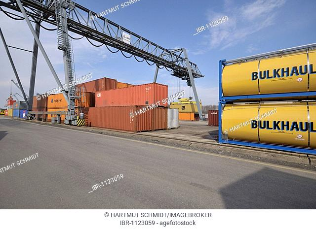 Container terminal Bonn, tank containers and Iso containers, next to it gantry crane lifting container on deck of ship, North Rhine-Westphalia, Germany