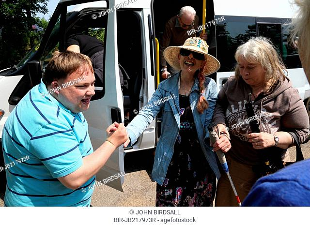 People with visual impairments getting off a minibus