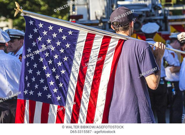 USA, New England, Massachusetts, Cape Ann, Rockport, Rockport Fourth of July Parade, young man with US flag, NR