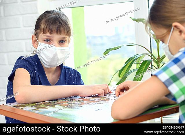 A girl in a medical mask plays board games and looked into the frame