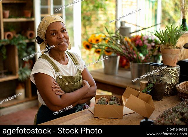 Portrait confident female florist boxing succulents in shop