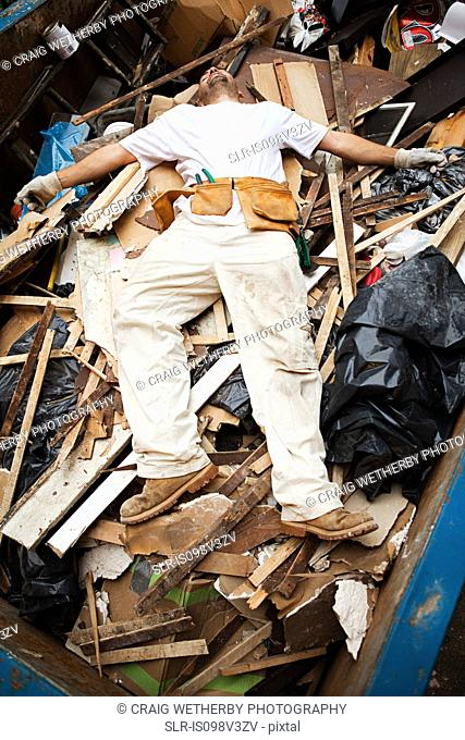 Man lying on top of pile of rubble in skip