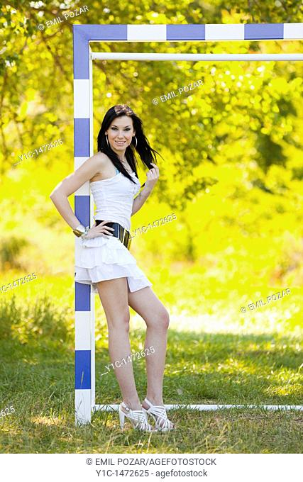 Attractive young woman is posing on the goal line