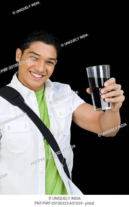 Man holding a glass of cola and smiling