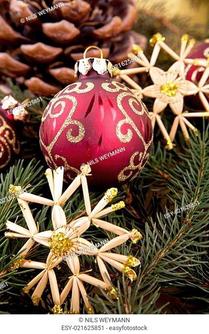 Festlicher Christbaumschmuck mit roten Weihnachtskugeln auf grü