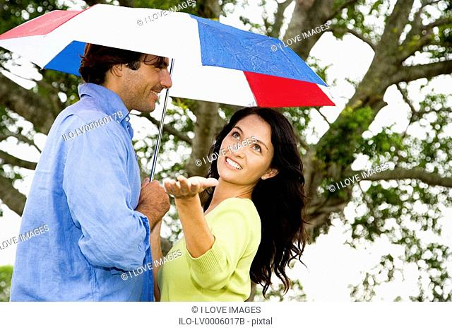 couple with umbrella walking in the park