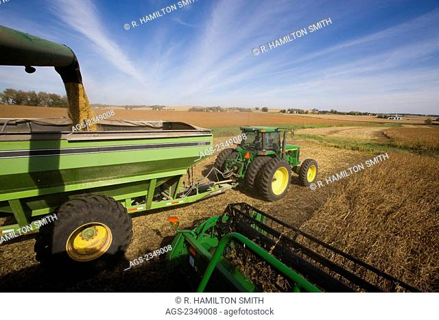 "Agriculture - View from the deck of a John Deere combine harvesting soybeans in Autumn while unloading into a grain wagon ""on-the-go"" / near Northland"