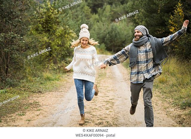 Happy young couple running on path in autumn