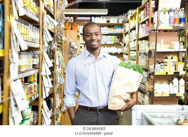 Portrait of man holding paper bag of shopping in health shop in health store, Johannesburg, South Africa