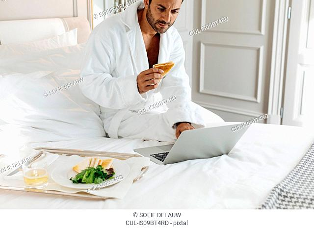 Man using laptop and having toast in suite