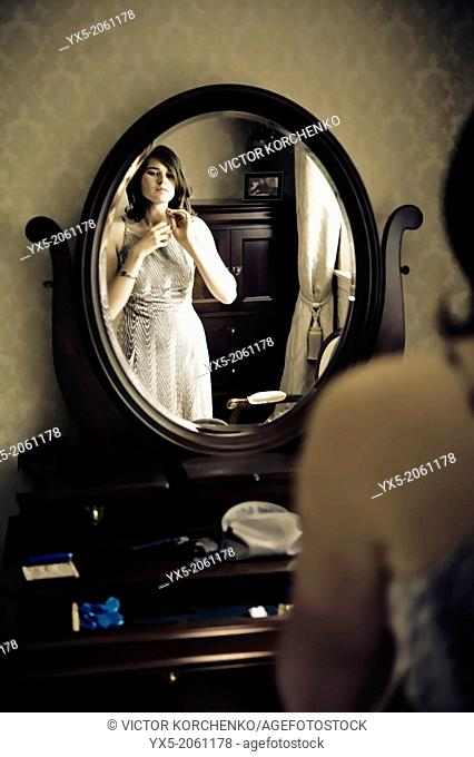Young woman dressing in front of a vanity mirror