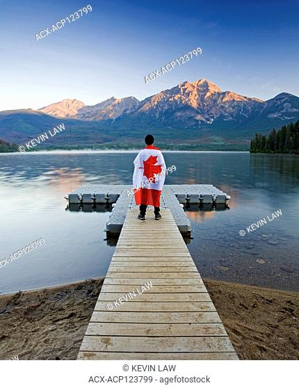 Male with Canadian flag walks on a dock at Pyramid Lake, Jasper National Park, Alberta, Canada