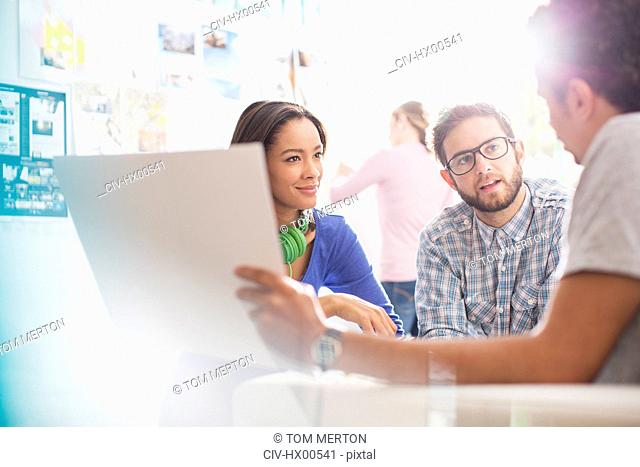 Creative business people discussing paperwork in office