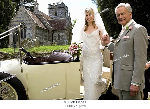 Father helping bride out of vintage car by church, smiling, portrait