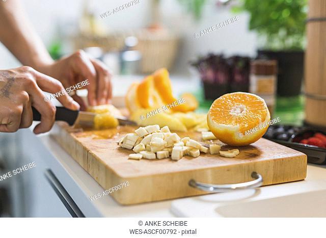 Woman preparing fruit on chopping board