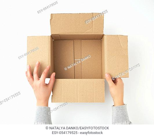 open empty square brown cardboard box for transportation and packaging of goods and two hands take out items, view from the top