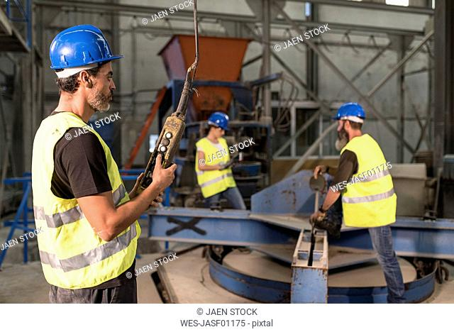 Worker using control in factory hall