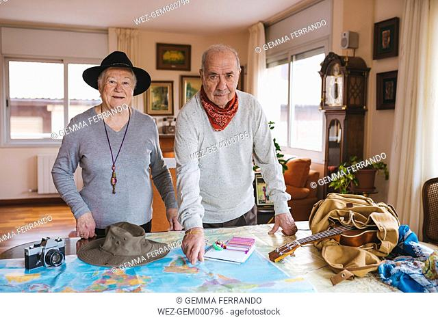 Elderly couple planning a trip on a map
