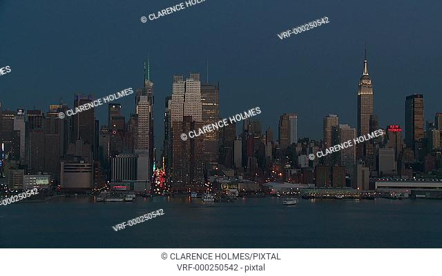 The city view during early twilight during a timelapse sequence of the Hudson River in front of the mid-town Manhattan skyline in New York City