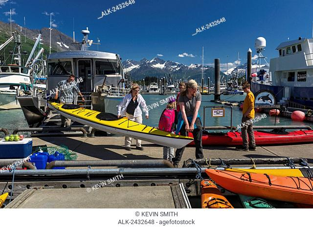 Visitors unload sea kayaks and gear from a water taxi at the Valdez small boat harbor, Prince William Sound, Southcentral Alaska