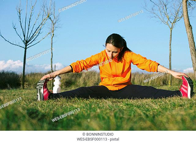 Young female jogger stretching