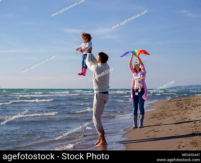 Family with little daughter resting and having fun with a kite at beach during autumn day