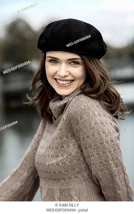 Portrait of happy young woman wearing beret and knitted dress