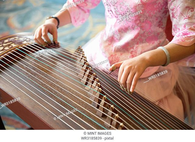 High angle close up of woman playing traditional Japanese Koto string instrument