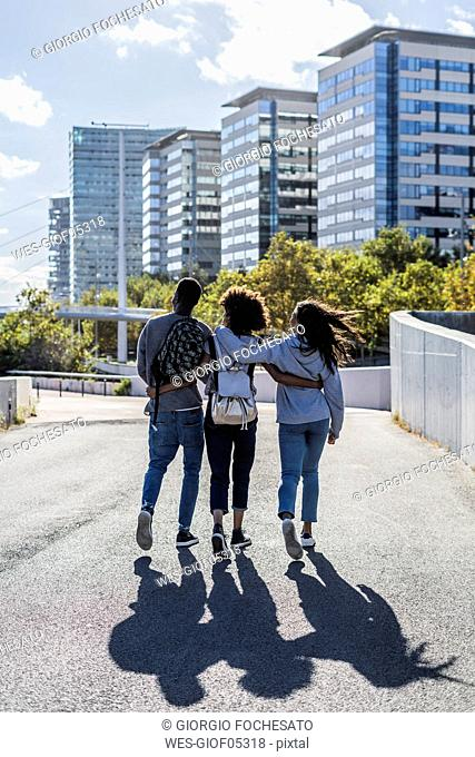 Three friends exploring the city, walking down the street, arm in arm