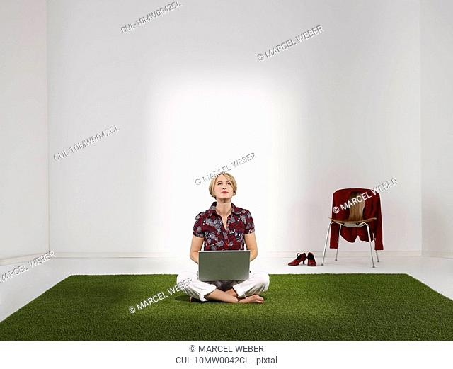 Woman sitting on grass with laptop