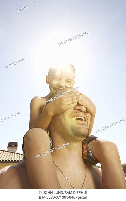 Young boy covering his father's eyes