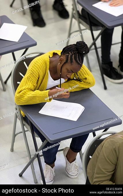 Focused high school girl student taking exam at desk in classroom
